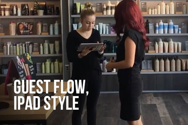 Salon employee standing with an Ipad talking to customer