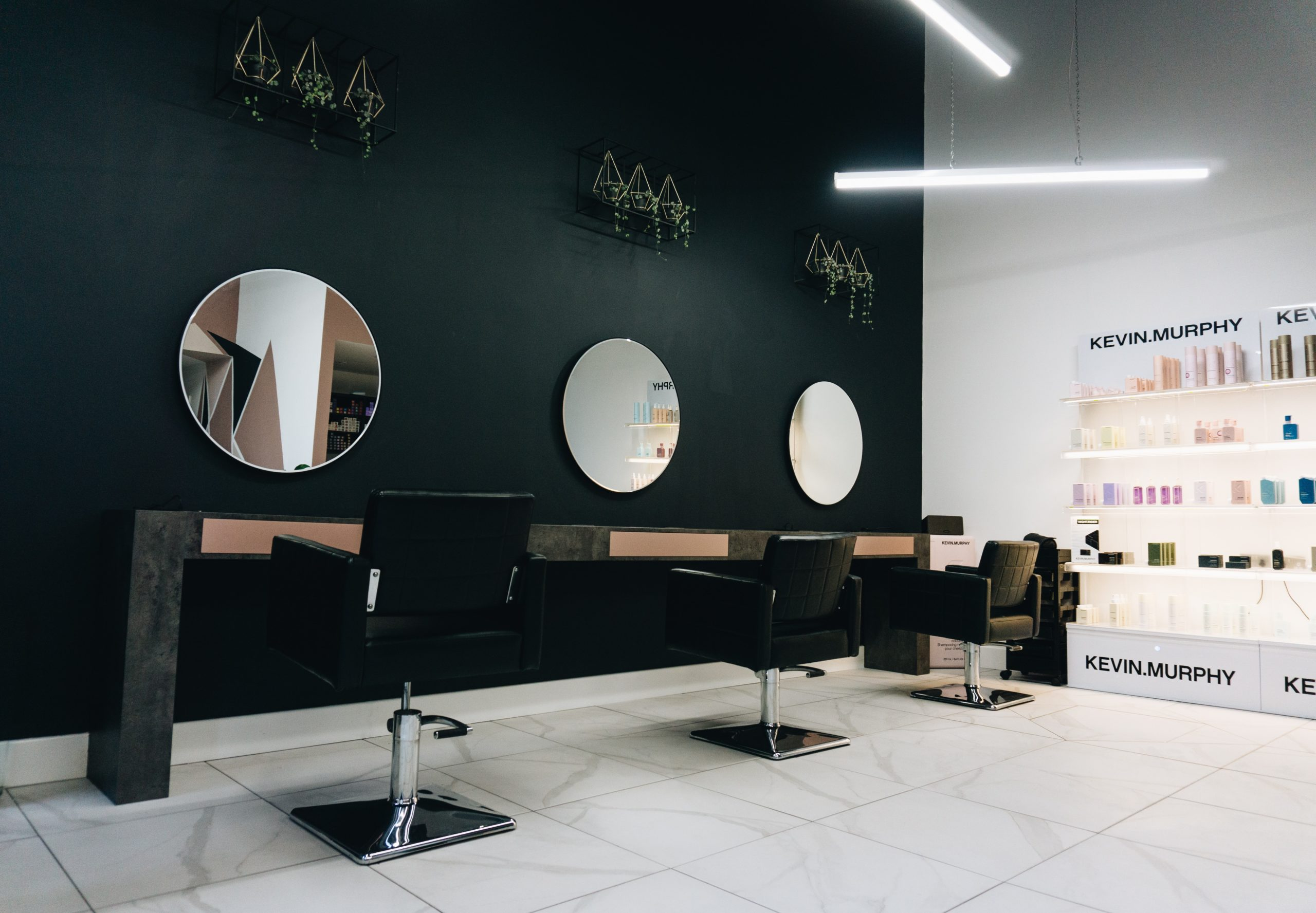 Minimal and modern salon decor ideas, a salon with round mirrors and black walls with decorative plants